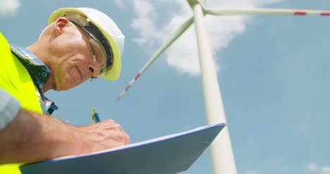 Engineer-Writing-On-Clipboard-While-Standing-Against-Windmill